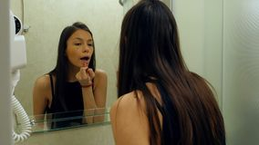 Hübsche, elegante Frau, die zu Hause Lippenstift im Badezimmer anwendet lizenzfreie stockfotos