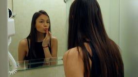 Hübsche, elegante Frau, die zu Hause Lippenstift im Badezimmer anwendet stock video