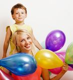 Hübsche Familie mit Farbe steigt auf weißem Hintergrund, blonde Frau mit kleinem Jungen auf Geburtstagsfeier im Ballon auf Lizenzfreies Stockfoto