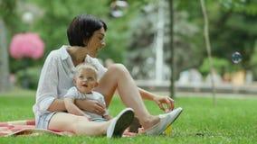 Hübsche Familienschlagblasen im Park stock footage