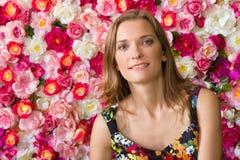 Hübsche Frau über Blumenhintergrund Stockbild