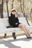 Hübsche Frau auf Bank mit Mobiltelefon Stockbild