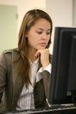 Hübsche Frau auf Computer Stockfoto