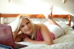 Hübsche Frau auf einem Bett mit Laptop Stockfotografie