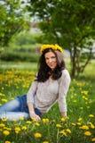 Hübsche Frau auf Löwenzahnfeld, glückliches nettes Mädchen, das an stillsteht Stockfotos