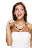 Hübsche Frau beißt auf ihren Gläsern, die oben schauen Lizenzfreie Stockfotos