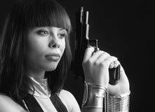 Hübsche Frau in den Handschellen mit einer Pistole. Stockbilder