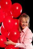 Hübsche Frau in der Bluse mit roten Ballonen Stockfoto