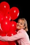 Hübsche Frau in der Bluse mit roten Ballonen Stockfotos