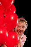 Hübsche Frau in der Bluse mit roten Ballonen Lizenzfreies Stockfoto