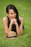 Hübsche Frau in der schwarzen Kleidung, die im Park liegt. Lizenzfreies Stockfoto