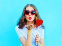 Hübsche Frau in der Sonnenbrille mit rotem Herzlutscher sendet einen Luftkuß über buntem Blau Stockfotos