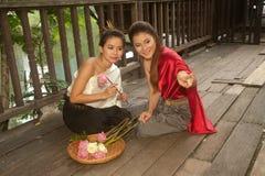Hübsche Frau in der thailändischen Art kleidet, wenn sie künstliche Blumen aufwirft. Lizenzfreies Stockfoto