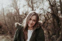 Hübsche Frau in der warmen Jacke mit Pelz posint an der Kamera im Freien lizenzfreie stockbilder