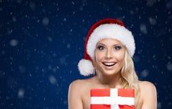 Hübsche Frau in der Weihnachtskappe übergibt das Geschenk, das mit rotem Papier eingewickelt wird Lizenzfreies Stockbild