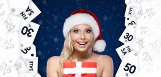 Hübsche Frau in der Weihnachtskappe übergibt Einzelteil zu einem großen Preis Stockfoto