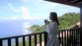 Hübsche Frau des jungen Brunette im Bademantel im Berg, nachdem Badekur zum Balkon kommt, trinkt das Kaffeegenießen stock footage
