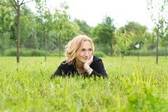 Hübsche Frau des Landes, die im Gras liegt lizenzfreie stockfotos