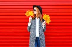 Hübsche Frau des Modeherbstes mit gelben Ahornblättern lizenzfreie stockfotografie