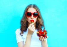 Hübsche Frau des Porträts mit vielen Erdbeere über buntem Blau stockbilder