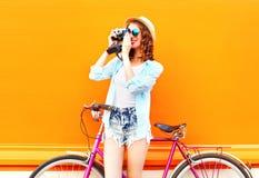 Hübsche Frau des Sommers mit Retro- Kamera und Fahrrad Stockbilder