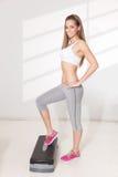 Hübsche Frau, die Übungen auf Schritt tut Stockbilder