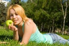 Hübsche Frau, die Apfel auf der Sommerlichtung isst Lizenzfreie Stockfotos