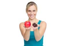 Hübsche Frau, die Apfel und Schokoladen zeigt Stockbild