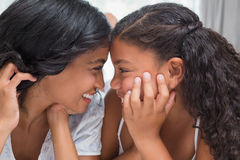 Hübsche Frau, die auf Bett mit ihrer Tochter lächelt an einander liegt Stockfotos