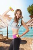 Hübsche Frau, die auf dem Strand ausarbeitet Lizenzfreies Stockbild
