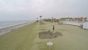 Hübsche Frau, die auf dem Strand, gesunder Lebensstil, Luftschuß entlang Ufer läuft stock video