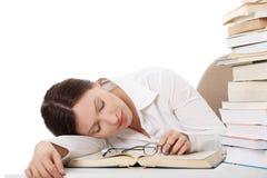 Hübsche Frau, die auf einem Buch schläft. Stockfotografie