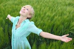 Hübsche Frau, die auf einem grünen Gebiet sich freut Stockfoto