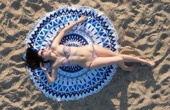 Hübsche Frau, die auf einer runden Strandtapisserie der Mandala liegt Stockfotos
