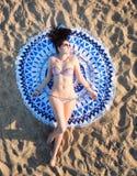 Hübsche Frau, die auf einer runden Strandtapisserie der Mandala liegt Lizenzfreie Stockfotografie