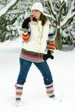 Hübsche Frau, die auf einer Zuckerstange im Schnee saugt Lizenzfreie Stockfotos