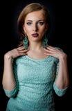 Hübsche Frau, die auf elegante tadellose grüne Mode aufwirft lizenzfreies stockbild