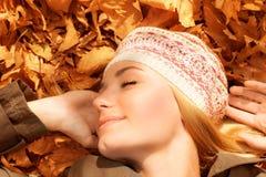 Hübsche Frau, die auf Falllaub schläft Lizenzfreie Stockfotos