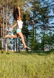 Hübsche Frau, die auf grünes Feld springt lizenzfreie stockfotografie