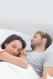 Hübsche Frau, die auf ihrem Ehemannkasten schläft Stockfotografie
