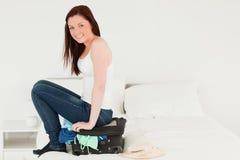 Hübsche Frau, die auf ihrem Koffer sitzt Stockfotos