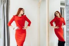 Hübsche Frau, die auf Kleidung in einer Montageabteilung versucht die Dame im roten Kleid wird im Spiegel reflektiert lizenzfreie stockfotos