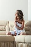 Hübsche Frau, die auf lederner Couch aufwirft Lizenzfreies Stockfoto