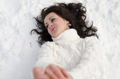Hübsche Frau, die auf Schnee liegt. Stockfotos