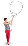 Hübsche Frau, die Ballonzeichnung hält Stockfotos