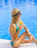 Hübsche Frau, die Cocktail nahe dem Swimmingpool genießt Stockbild