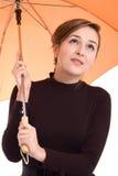 Hübsche Frau, die darunterliegend von einem Regenschirm schaut Lizenzfreie Stockbilder