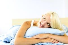 Hübsche Frau, die in das träumende Bett legt Lizenzfreies Stockfoto