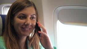 Hübsche Frau, die den Spaß spricht am Telefon, sitzend im Flugzeug-Fenster hat stock video