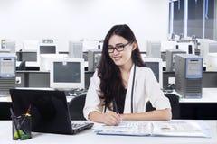 Hübsche Frau, die an der Kamera im Büro lächelt Lizenzfreie Stockbilder